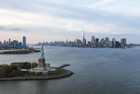 Statue of Liberty by island in city against cloudy sky 11100059028| 写真素材・ストックフォト・画像・イラスト素材|アマナイメージズ