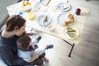 High angle view of mother feeding breakfast to son at table 11100059329| 写真素材・ストックフォト・画像・イラスト素材|アマナイメージズ