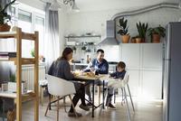 Parents looking at son sitting on high chair while having breakfast in kitchen 11100059339| 写真素材・ストックフォト・画像・イラスト素材|アマナイメージズ
