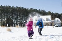 Siblings playing with snow on field against clear sky 11100059959| 写真素材・ストックフォト・画像・イラスト素材|アマナイメージズ