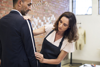 Mature female fashion designer taking measurement on businessman while standing at workshop 11100060121| 写真素材・ストックフォト・画像・イラスト素材|アマナイメージズ