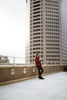 Full length of woman using smart phone while leaning on railing at terrace against building 11100060795| 写真素材・ストックフォト・画像・イラスト素材|アマナイメージズ