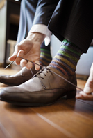 Low section of bridegroom tying shoelace at home 11100061560| 写真素材・ストックフォト・画像・イラスト素材|アマナイメージズ