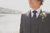 Midsection of smiling bridegroom standing at lakeshore 11100061562| 写真素材・ストックフォト・画像・イラスト素材|アマナイメージズ