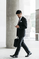 Full length of businessman using smart phone while walking at colonnade 11100061924| 写真素材・ストックフォト・画像・イラスト素材|アマナイメージズ