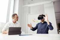 Engineer with tablet computer looking at coworker examining virtual reality simulator in office 11100062146| 写真素材・ストックフォト・画像・イラスト素材|アマナイメージズ
