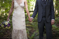 Midsection of newlywed couple holding hands while standing on field in park 11100062417| 写真素材・ストックフォト・画像・イラスト素材|アマナイメージズ