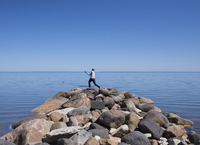 Rear view of man standing on rocky beach against clear blue sky 11100062928| 写真素材・ストックフォト・画像・イラスト素材|アマナイメージズ