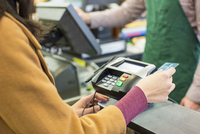 Midsection of woman paying bill with credit card at supermarket 11100063669| 写真素材・ストックフォト・画像・イラスト素材|アマナイメージズ