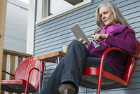 Low angle view of woman doing online shopping while sitting on chair at porch 11100063702| 写真素材・ストックフォト・画像・イラスト素材|アマナイメージズ