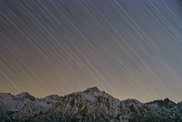 Low angle view of star trails over snowcapped mountain at night 11100064182| 写真素材・ストックフォト・画像・イラスト素材|アマナイメージズ