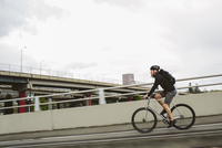Side view of male commuter with backpack riding bicycle on bridge against sky 11100064371| 写真素材・ストックフォト・画像・イラスト素材|アマナイメージズ