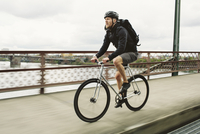 Male commuter riding bicycle on bridge over river against cloudy sky 11100064373| 写真素材・ストックフォト・画像・イラスト素材|アマナイメージズ