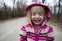 Close-up of smiling girl with eyes closed standing on road 11100064665| 写真素材・ストックフォト・画像・イラスト素材|アマナイメージズ