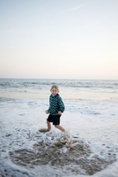 Smiling boy playing on shore at beach against sky 11100064680| 写真素材・ストックフォト・画像・イラスト素材|アマナイメージズ