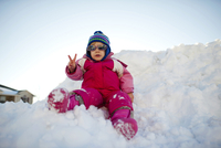 Girl in sunglasses showing peace sign while sitting on snow against clear sky 11100064691| 写真素材・ストックフォト・画像・イラスト素材|アマナイメージズ