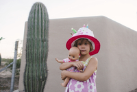 Portrait of girl in hat holding doll while standing by cactus 11100064792| 写真素材・ストックフォト・画像・イラスト素材|アマナイメージズ