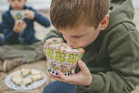 Boy drinking from cup while sitting at beach with brother in background 11100064810| 写真素材・ストックフォト・画像・イラスト素材|アマナイメージズ