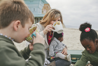 Family drinking from cups while sitting at beach 11100064812| 写真素材・ストックフォト・画像・イラスト素材|アマナイメージズ