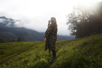 Full length of woman wrapped in blanket standing on grassy field during foggy weather 11100065235| 写真素材・ストックフォト・画像・イラスト素材|アマナイメージズ
