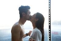 Side view of romantic couple kissing while standing by window at home 11100065348| 写真素材・ストックフォト・画像・イラスト素材|アマナイメージズ