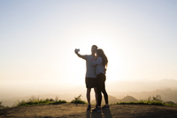 Couple taking selfie through smart phone while standing on mountain against clear sky 11100065354| 写真素材・ストックフォト・画像・イラスト素材|アマナイメージズ
