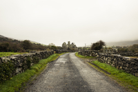 Empty road amidst stone wall against sky during foggy weather 11100065428| 写真素材・ストックフォト・画像・イラスト素材|アマナイメージズ