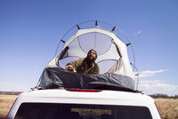 Low angle view of thoughtful man sitting in tent on car roof against blue sky 11100065772| 写真素材・ストックフォト・画像・イラスト素材|アマナイメージズ
