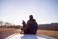 Rear view of man sitting with dog on car roof against clear sky 11100065788| 写真素材・ストックフォト・画像・イラスト素材|アマナイメージズ