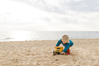 Boy playing with toy truck at beach against cloudy sky 11100065972| 写真素材・ストックフォト・画像・イラスト素材|アマナイメージズ
