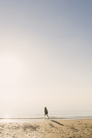 Side view of boy wearing life jacket running in sea during foggy weather 11100066094| 写真素材・ストックフォト・画像・イラスト素材|アマナイメージズ