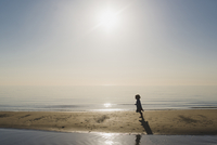 Silhouette boy running at beach against sky during sunny day 11100066100| 写真素材・ストックフォト・画像・イラスト素材|アマナイメージズ