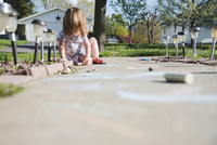 Girl drawing with chalks while sitting on footpath 11100066105| 写真素材・ストックフォト・画像・イラスト素材|アマナイメージズ