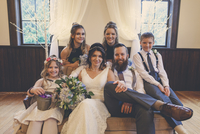 Portrait of newlywed couple sitting by pageboy and flower girl with bridesmaids on sofa during wedding ceremony 11100066985| 写真素材・ストックフォト・画像・イラスト素材|アマナイメージズ
