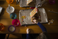 High angle view of girl decorating gingerbread house on table 11100068033| 写真素材・ストックフォト・画像・イラスト素材|アマナイメージズ