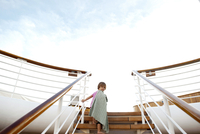 Low angle view of girl climbing steps in cruise ship against sky 11100068659| 写真素材・ストックフォト・画像・イラスト素材|アマナイメージズ