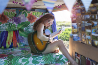 Woman playing guitar while sitting in motor home 11100069269| 写真素材・ストックフォト・画像・イラスト素材|アマナイメージズ