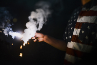 Midsection of man wearing American Flag t-shirt while holding sparkler during night 11100069282| 写真素材・ストックフォト・画像・イラスト素材|アマナイメージズ