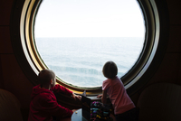 Siblings looking at sea while standing by porthole in cruise ship 11100069629| 写真素材・ストックフォト・画像・イラスト素材|アマナイメージズ