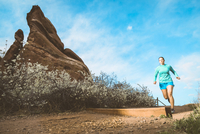 Determined sportswoman jogging on dirt trail by rock formation against sky 11100069863| 写真素材・ストックフォト・画像・イラスト素材|アマナイメージズ