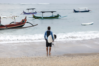Rear view of man looking at sea while carrying surfboard on shore 11100070554| 写真素材・ストックフォト・画像・イラスト素材|アマナイメージズ