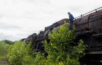 Low angle view of man on abandoned train against sky 11100070586| 写真素材・ストックフォト・画像・イラスト素材|アマナイメージズ