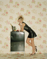 Young woman wearing black dress leaning on cabinet 11107003459| 写真素材・ストックフォト・画像・イラスト素材|アマナイメージズ